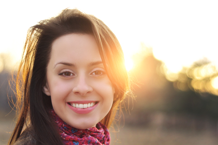 Image of a face beautiful female model in a colorful cotton scarf closeup on sunset background