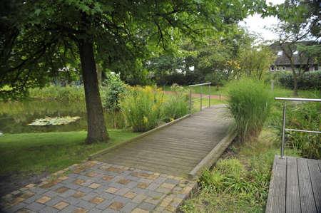 Деревянный мост через речку в городском парке Фото со стока