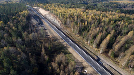 Road in the autumn forest. Travelling in northern forest
