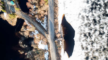Aerial drone view of a branch road, white snowy land and road, trees