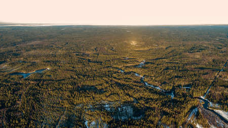 Aerial view of old asphalt road in the spring forest. Snow melts on the side of the road and between the trees