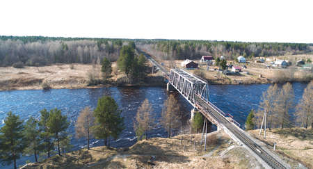 Aerial view on the rail bridge across the river in rural place in spring