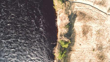 Amazing aerial shot of beautiful dark river shore.