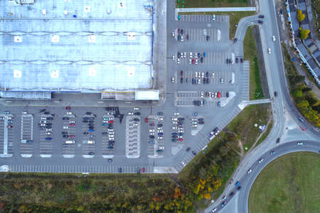 Aerial view of city landscape and big building supermarket mall, parking lot with parked cars on rainy day. Drone photography.