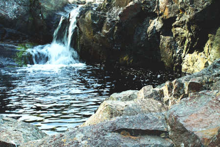 Small waterfall in Karelia and rocks in spring
