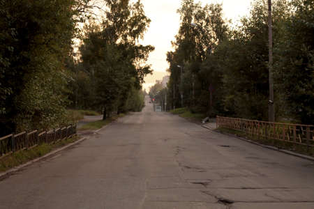 The empty street at night with rural bad asphalt road in summer. Zdjęcie Seryjne