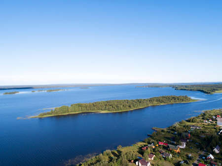 Aerial view on lake shore in summer day with green forest
