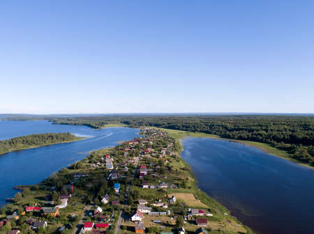 Aerial view on lake shore and private houses in summer day with green forest
