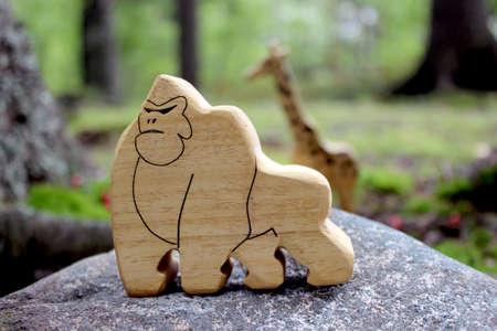 Fairy-tale wooden gorilla toy standing on the wild rock. Zdjęcie Seryjne
