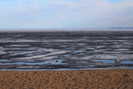 Large lake melting in late spring. Freshwater lake shore with sandy beach, blue water and floating ice formations and snow
