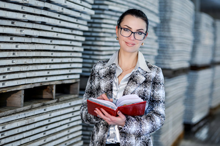 Warehouse worker keeps a record of the goods. Warehouse with glasses in the process. Young beautiful girl writes in notebook product balance in stock thereby fulfilling their office job.