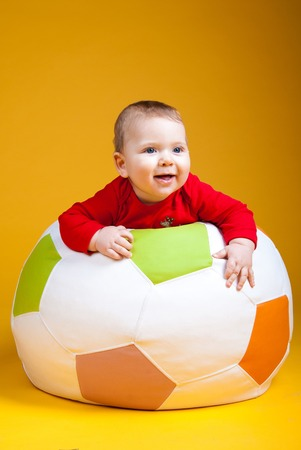 taper: A child plays on the ball with toys on a yellow background