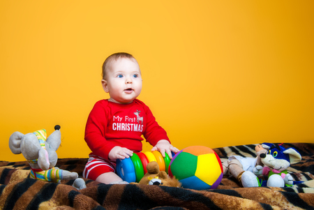 tot: A child plays on the ball with toys on a yellow background
