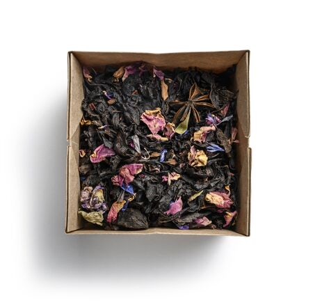 Black tea with natural aromatic additives. Top view on white background
