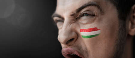 A screaming man with the image of the countrys national flag on his face Stock fotó