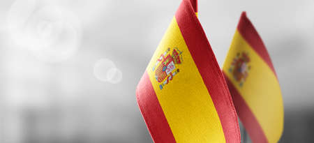 Small national flags of the Spain on a light blurry background Standard-Bild