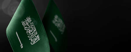 Small national flags of the Saudi Arabia on a dark background