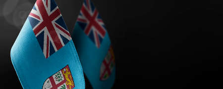 Small national flags of the Fiji on a dark background