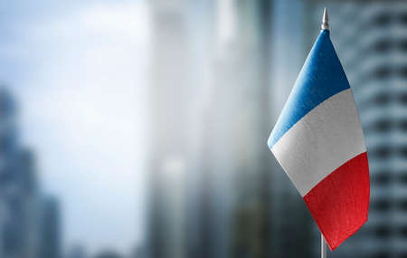 A small flag of France on the background of a blurred background