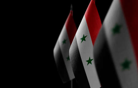 Small national flags of the Syria on a black background