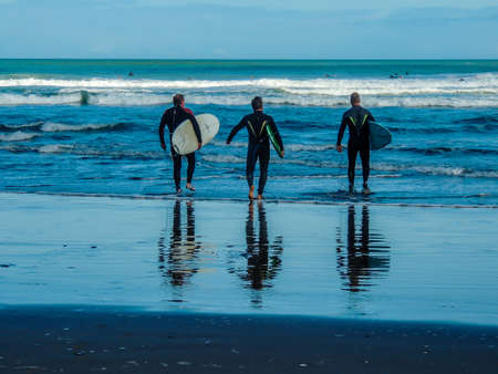 Surfing at Maukatia (Maori Bay) and Muriwai Beach. Auckland, New Zealand