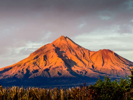 Mount Taranaki is an active volcano that sits ont he west coast of new zeland in the taranaki region. It is aslo called mount edgemont. Archivio Fotografico - 101876951