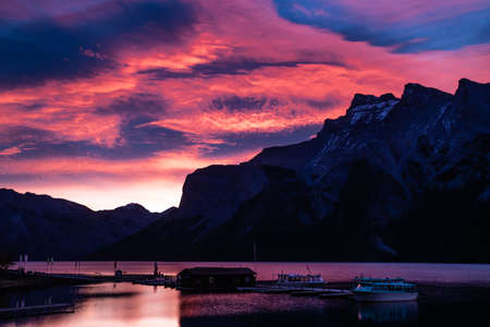 sun rises a brillant red over lake minnewanka, in banff national park Stock Photo