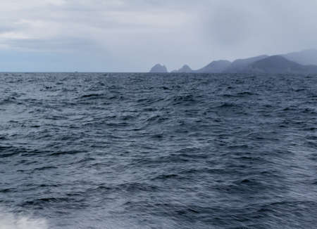 Stormy, skies, blue skies, dotted rock islands are a pleasant view durinf a cruise around the Bay of Islands Stok Fotoğraf