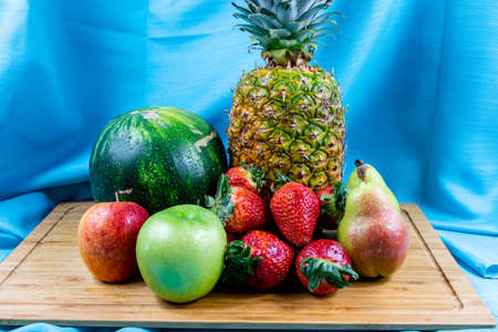 Colourful assorted raw fruits on a wooden cutting board. Calgary, Alberta, Canada