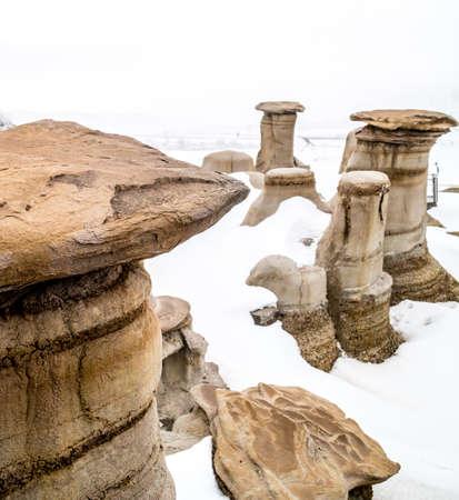 Late blast of snow tries to hide the Hoodoos in the badlands. Drumheller Alberta, Canada. Stock Photo