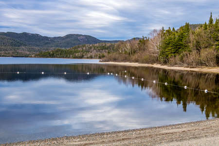 Reflection on the calm side of the pond. Barachois Pond Provincial Park, Newfoundland, Canada
