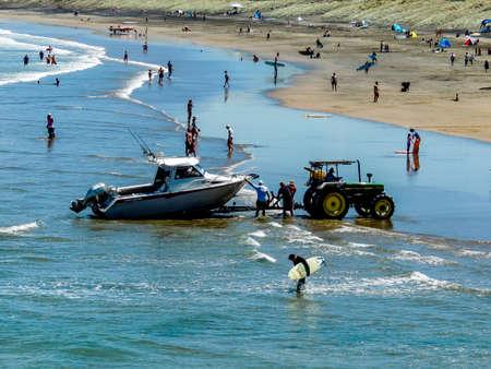 People fishing off the rocks at Murawai Beach, Auckland, New Zealand