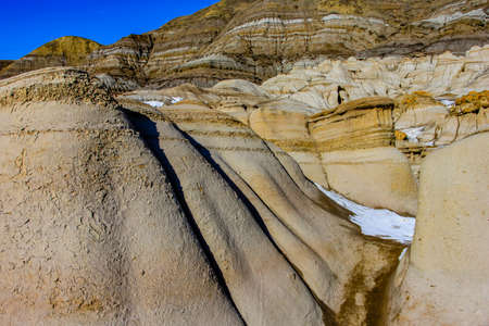 Last snow of the year clings to the Badlands. Drumheller, Alberta, Canada