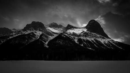 The three isters at sunset on a winters night with gloomy clouds over head. Canmore, Alberta Canada
