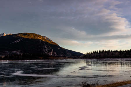 Sun rises over the lake and reflects the mountains. Lac de Arc, Alberta, Canada Banque d'images