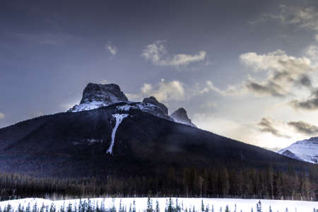 Three Sisters with clouds hovering near by wait for the sun to set. Canmore, Alberta, Canada