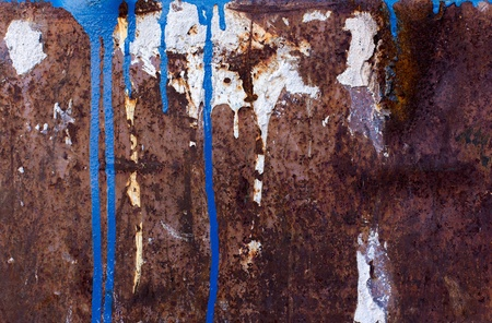corroded: Blue and white paint spill on rusted metal texture