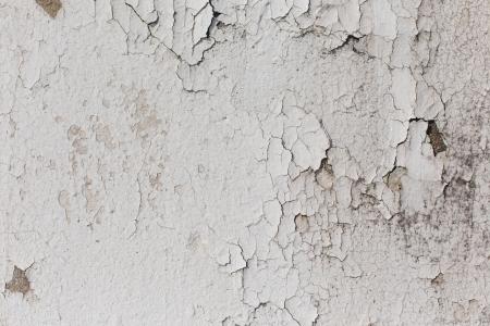 white paint peeling away from concrete pillar photo