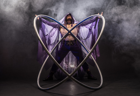 Fairy-tale character assassin in a purple cloak with a hood with two large cyr wheel hoops Stock Photo