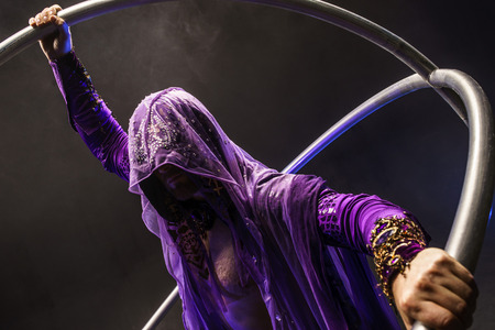 Fairy-tale character assassin in a purple cloak with a hood with two large cyr wheel hoops Imagens