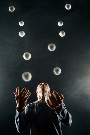 Blond juggler with white balls on black background 写真素材 - 106123519