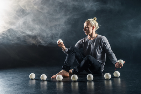 Blond juggler sitting on the floor with white balls on black background