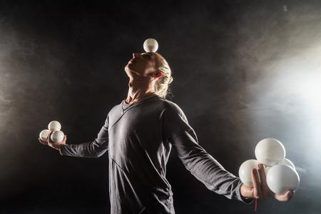 Jongleur blond garder l'équilibre boules blanches sur fond noir