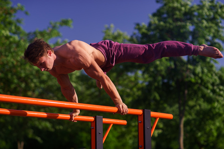 Muscular man making planche on the street. Street workout Stock Photo
