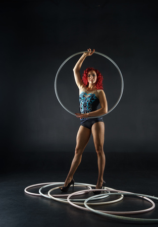 beautiful female red hair circus artist with a hoops