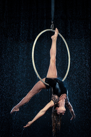 Young beautiful slim circus artist on aerial hoop posing on a black aqua studio background.