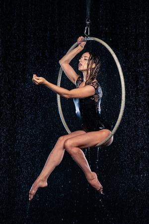 Beautiful female acrobat sitting in aerial hoop under rain on black background