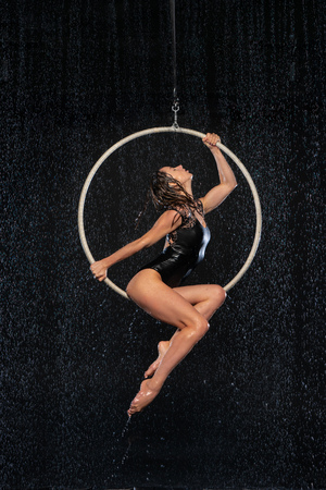 Beautiful female acrobat sitting in aerial hoop under rain on black background
