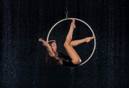 A young girl performs the acrobatic elements in the aerial hoop. Black Aqua Studio