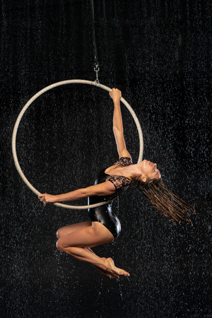 A young girl performs the acrobatic elements in the aerial ring. Aqua Studio shooting performances on a black background